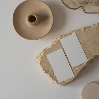 Postura plana de cartões de folha de papel em branco com flor, pedra de mármore em branco