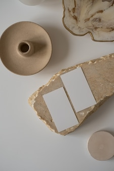Postura plana de cartões de folha de papel em branco com flor, pedra de mármore Foto Premium