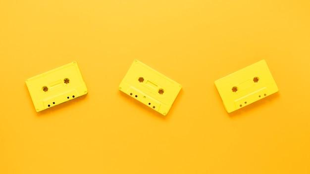 Postura plana de cassetes em fundo amarelo