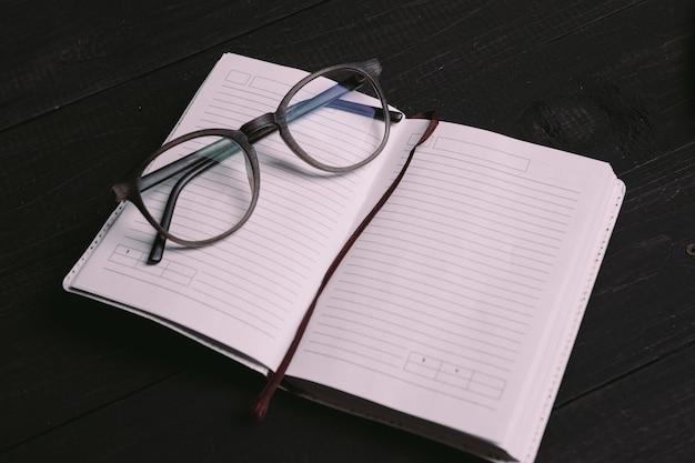 Postura plana de coisas de viagem no bloco de notas com óculos na placa de madeira