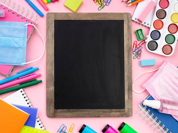 Postura plana de colorido de volta aos artigos de papelaria da escola com quadro-negro