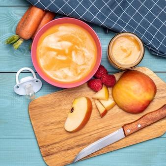 Postura plana de comida para bebê em uma tigela com frutas e cenouras