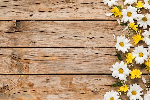 Postura plana de conceito floral na mesa de madeira