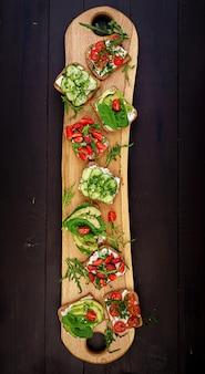 Postura plana de configuração de mesa de jantar vegetariano saudável. sanduíches com tomate, pepino, abacate, morango, ervas e azeitonas, lanches. alimentação limpa, comida vegana