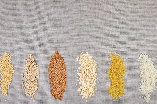 Postura plana de conjunto de heap vários grãos e cereais bulgur, arroz, aveia, trigo sarraceno, sementes de trigo cuscuz em fundo cinza, espaço de cópia, espaço para texto, vista superior.