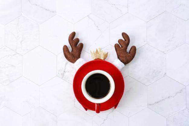 Postura plana de copo de café preto vermelho com bandana de rena para celebração de natal em mármore branco, conceito de férias de inverno