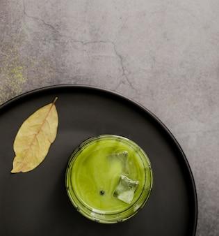 Postura plana de copo de chá matcha com cubos de gelo
