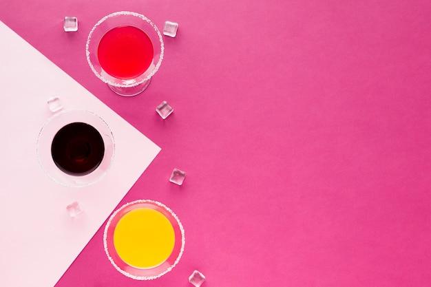 Postura plana de copos de cocktails com cubos de gelo e espaço para texto