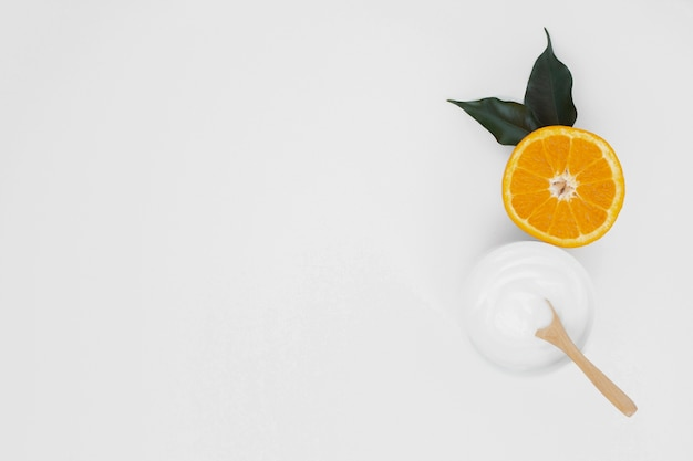 Postura plana de corpo manteiga crean e fatia de laranja com espaço de cópia