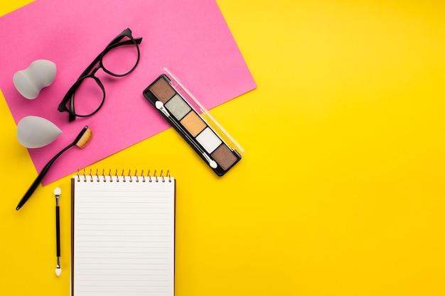 Postura plana de cosmético em fundo amarelo, com espaço de cópia