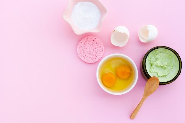 Postura plana de creme e ovos no bacground rosa com espaço de cópia
