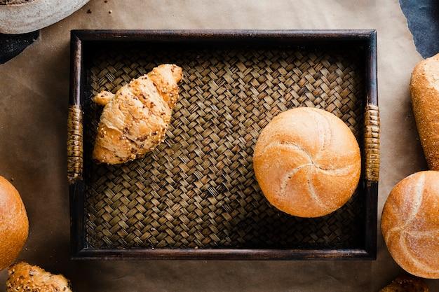 Postura plana de croissant e pão em uma cesta