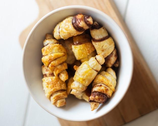 Postura plana de croissants de chocolate na tigela