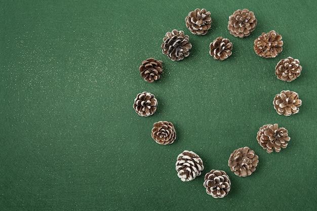 Postura plana de decorações de natal de pinha em uma superfície verde