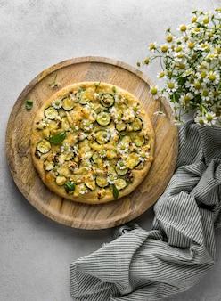 Postura plana de deliciosa pizza cozida com buquê de flores de camomila