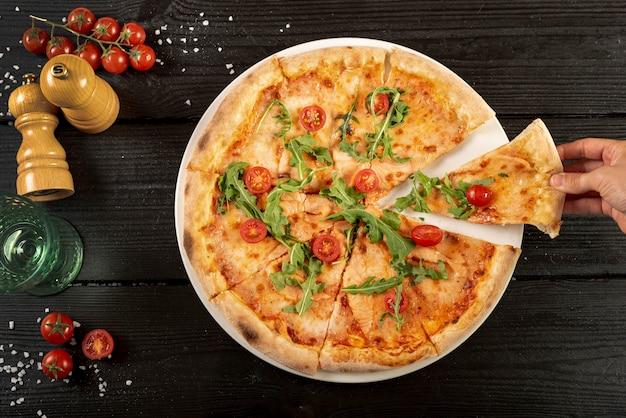 Postura plana de deliciosa pizza na mesa de madeira