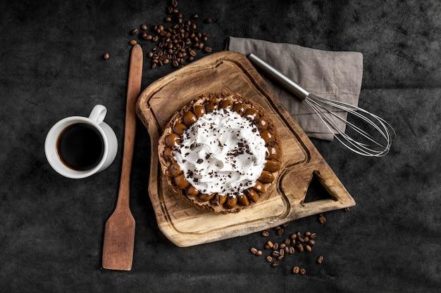 Postura plana de delicioso bolo com batedor e café