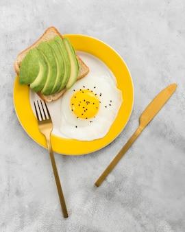 Postura plana de delicioso café da manhã com abacate