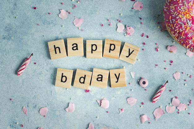 Postura plana de desejo feliz aniversário em letras de madeira com donut