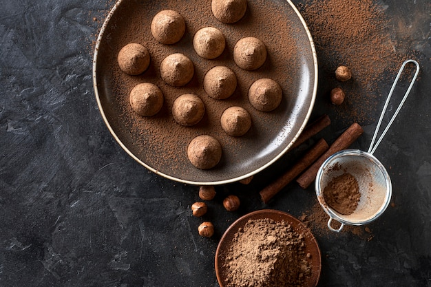 Postura plana de doces de chocolate com cacau em pó e paus de canela