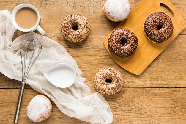 Postura plana de donuts com granulado na superfície de madeira