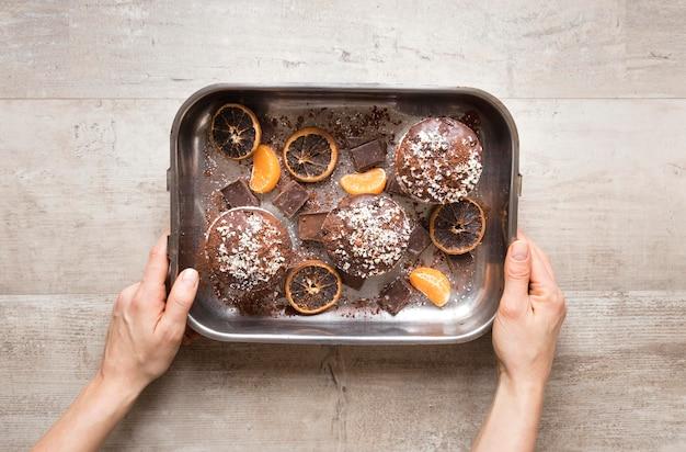 Postura plana de donuts na bandeja de metal com frutas cítricas secas