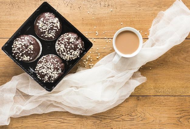 Postura plana de donuts no prato com café e tecido