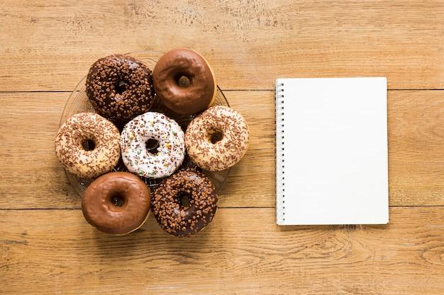 Postura plana de donuts no prato com notebook