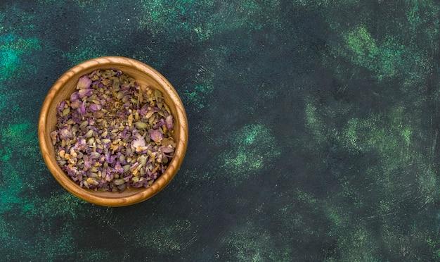 Postura plana de ervas medicinais em uma tigela com espaço de cópia