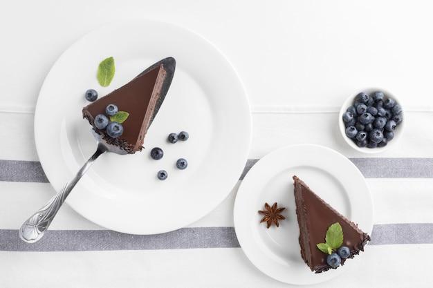 Postura plana de fatias de bolo de chocolate em pratos com mirtilos