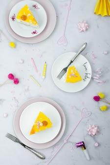 Postura plana de fatias de bolo em placas com decorações de aniversário