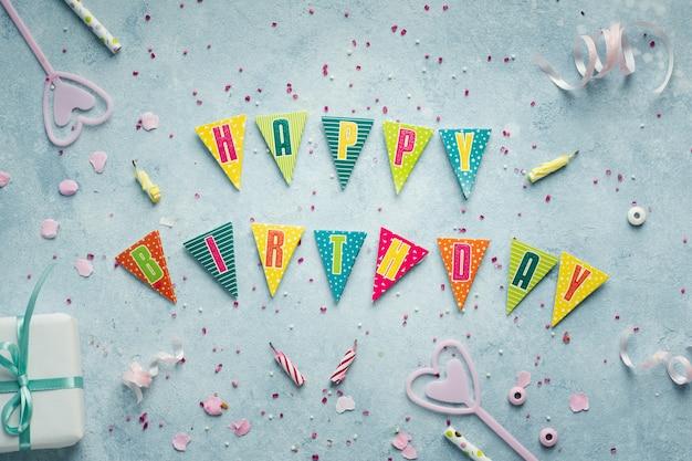 Postura plana de feliz aniversário desejo na guirlanda com presente