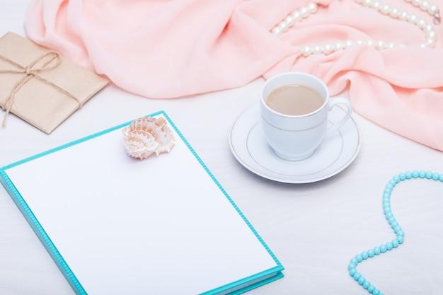 Postura plana de folha de papel em branco com uma xícara de café e jóias