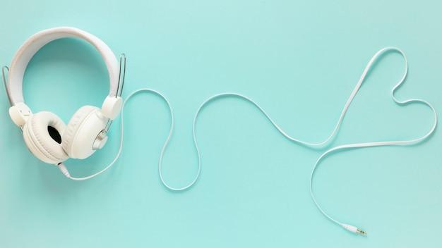 Postura plana de fones de ouvido no fundo liso