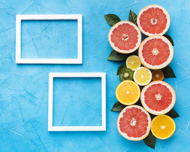 Postura plana de frutas cítricas e quadros com espaço de cópia