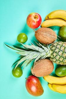 Postura plana de frutas exóticas sobre fundo azul.