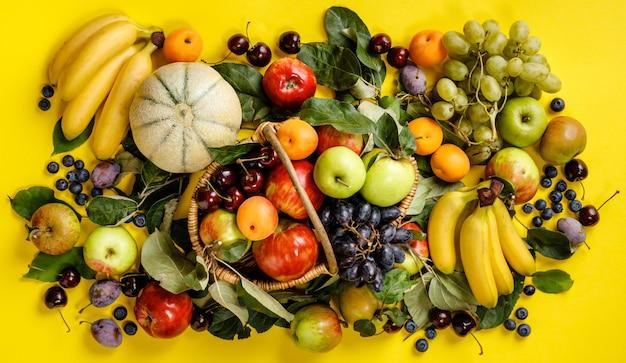 Postura plana de frutas frescas e bagas em amarelo