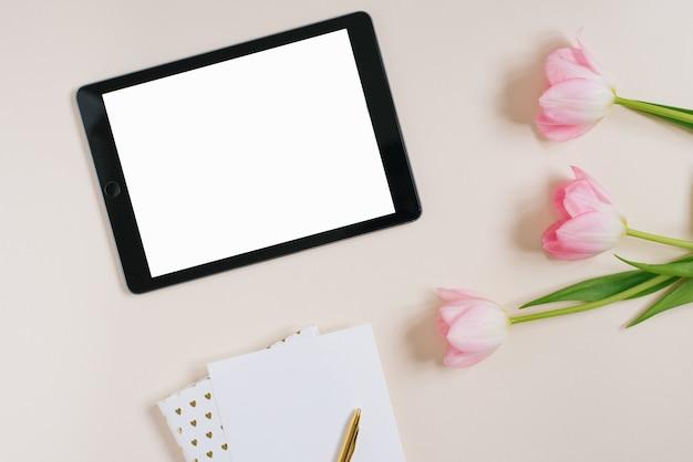 Postura plana de fundo de primavera de tulipas cor de rosa com maquete de tablet, copie o espaço para texto. dia das mães ou dia dos namorados