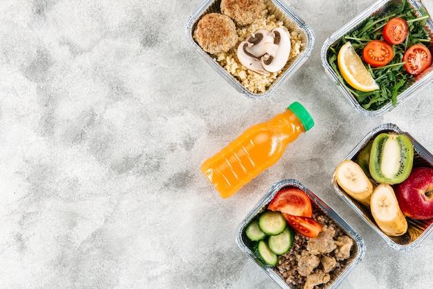Postura plana de garrafa de suco de laranja com refeições em caçarolas e espaço para texto
