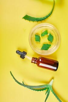 Postura plana de gel de aloe vera de planta de ingredientes naturais de cuidados da pele caseiros, skinimalismo, beleza lenta em fundo amarelo, espaço de cópia.