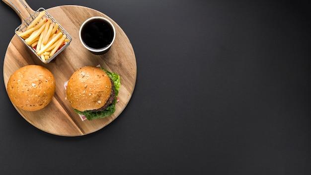 Postura plana de hambúrgueres e batatas fritas com espaço de cópia