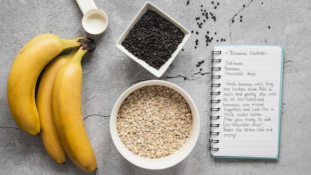 Postura plana de ingredientes alimentares com bananas e caderno