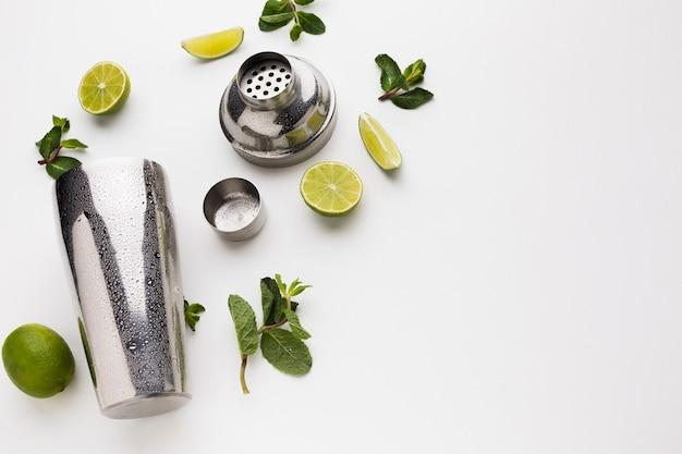 Postura plana de ingredientes de coquetel com agitador e limão