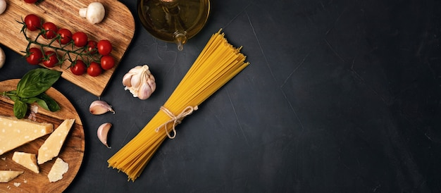 Postura plana de ingredientes para cozinhar macarrão italiano. espaguete, tomate, óleo, alho, parmesão. vista superior do conceito tradicional da culinária italiana