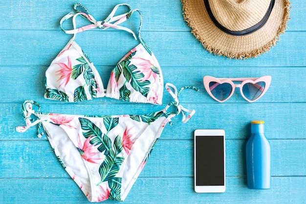 Postura plana de itens de verão com biquíni colorido; smartphone; oculos escuros; chapéu de palha; suncream e smartphone na mesa de madeira azul; copie o espaço; vista do topo. conceito de verão tropical.
