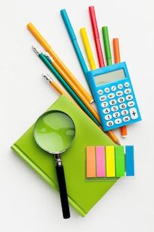 Postura plana de itens essenciais da escola com calculadora e livro