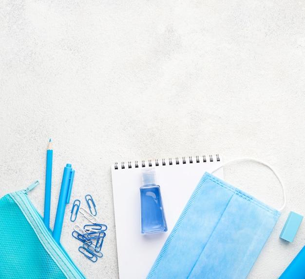 Postura plana de itens essenciais da escola com clipes de papel e máscara médica