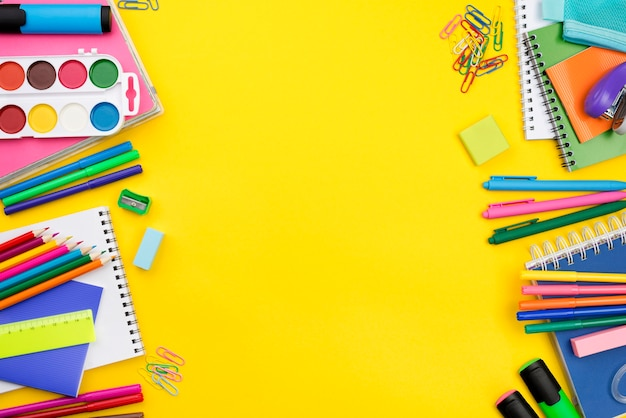 Postura plana de itens essenciais da escola com lápis coloridos e espaço de cópia