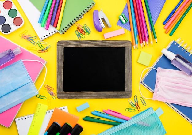 Postura plana de itens essenciais da escola com lápis coloridos e quadro-negro