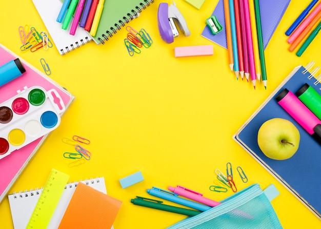 Postura plana de itens essenciais da escola com lápis coloridos